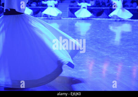 Whirling dervishes perform the Mevlevi Sema Ceremony at 740th anniversary of the death of Sufi teacher Mevlana Jalaladdin - Stock Photo