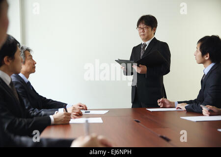 Japanese business people attending board meeting - Stock Photo