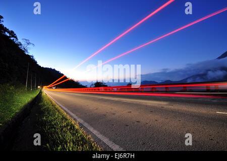 Taillight of a vehicles on a road, twilight blue sky. Kota Kinabalu highway, sabah Malaysia. - Stock Photo