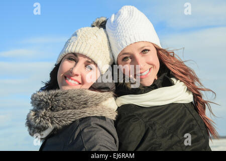 Two young girls having fun in winter park - Stock Photo