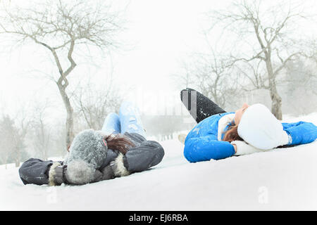 Two happy young girls having fun in winter park - Stock Photo