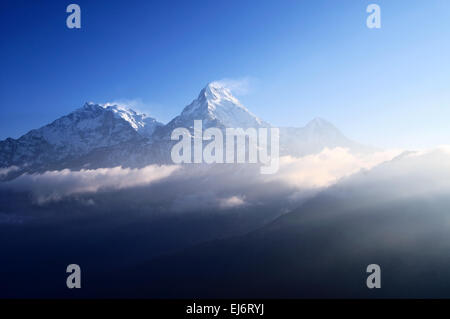 Dramatic sun light sunrise over snow capped mountain Machapuchare Fish Tail mountain in Annapurna Himalaya. - Stock Photo