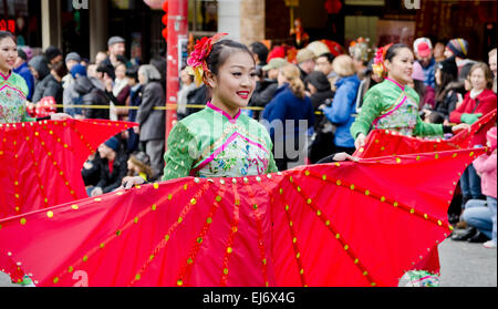 Asian woman performers carrying large red fans as they take part in the Lunar New Year's parade in Chinatown in - Stock Photo