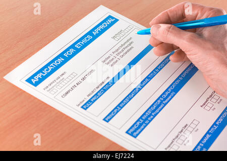 Hand with Pen Writing on Ethics Approval Application - Stock Photo