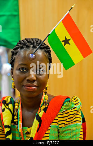 Young woman from Ghana displaying the national flag of her country on her forhead, Ghana - Stock Photo