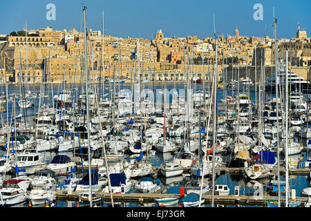 Sailing boats moored in the Grand Harbour Marina in Vittoriosa against the scenic background of Valletta, Malta - Stock Photo