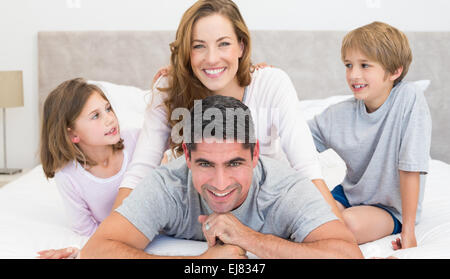 Happy parents and children in bed - Stock Photo