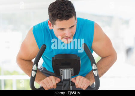 Serious man working out at spinning class - Stock Photo