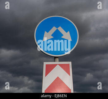 Road sign against cloudy sky - Stock Photo