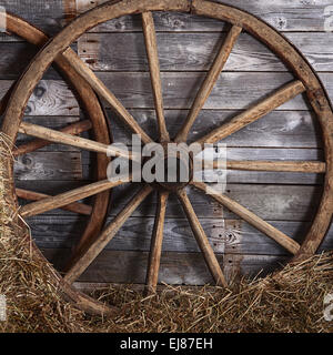Old wooden wheel on a hay - Stock Photo