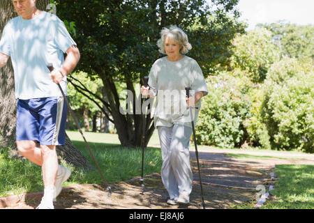 Mature couple Nordic walking at park - Stock Photo