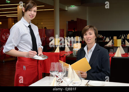 young waitress listed order - Stock Photo