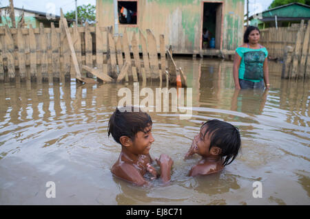 2015 flooding in Brazilian Amazon - children play in the dirty waters of Acre river at Taquari district, Rio Branco - Stock Photo
