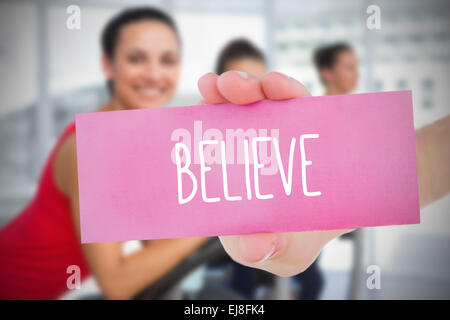 Woman holding pink card saying believe - Stock Photo