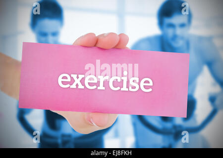 Woman holding pink card saying exercise - Stock Photo