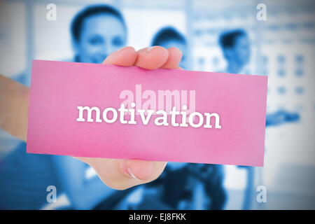Woman holding pink card saying motivation - Stock Photo