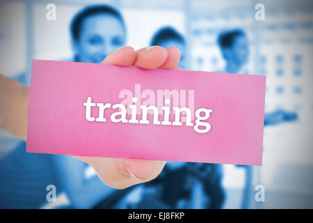 Woman holding pink card saying training - Stock Photo