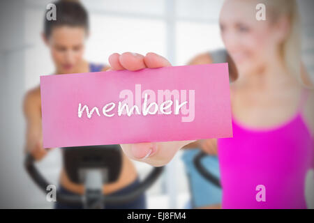 Fit blonde holding card saying member - Stock Photo