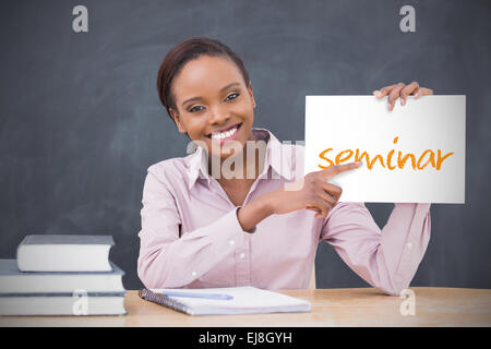 Happy teacher holding page showing seminar - Stock Photo
