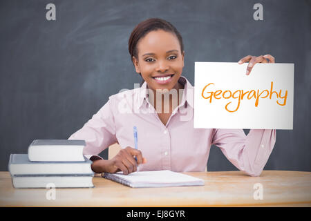 Happy teacher holding page showing geography - Stock Photo