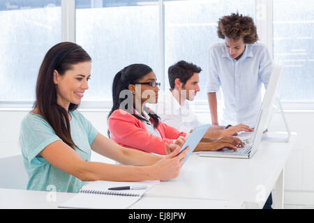 Workers on tablets and laptops - Stock Photo