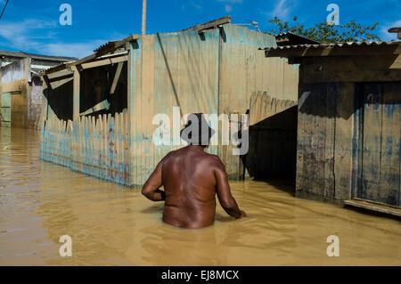 2015 flooding in Brazilian Amazon, Black man crosses flooded street in Taquari district, Rio Branco city, Acre State. - Stock Photo