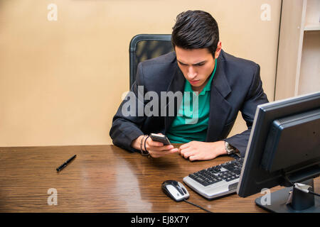Handsome young businessman at desk in his office dialing on phone to make a call or typing a text message - Stock Photo