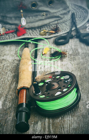 Fly fishing reel with old hat on bench - Stock Photo