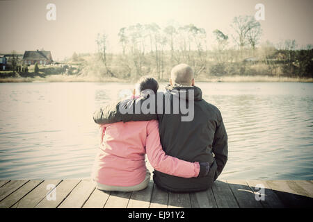 Retro sepia stylized picture of a couple sitting on wooden pier by lake. - Stock Photo