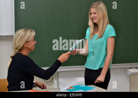 Teacher presents the student her notebook - Stock Photo