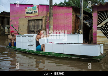 2015 flooding in Brazilian Amazon,  woman transports kitchen furniture in small boat through flooded street at Triangulo - Stock Photo
