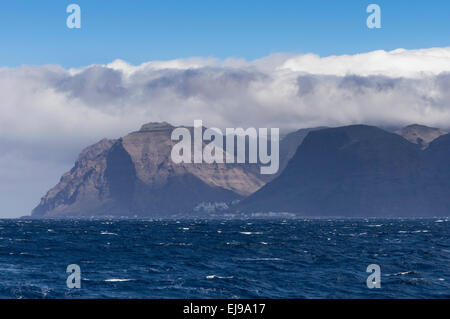 The coast of La Gomera from the sea with clouds over the land with town of Valle Gran Rey in view - Stock Photo