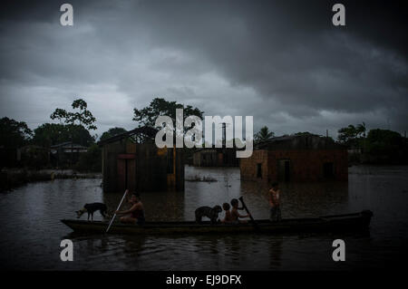 2015 flooding in Brazilian Amazon, displaced family and dogs in boat rows in flooded street under rain at Taquari - Stock Photo