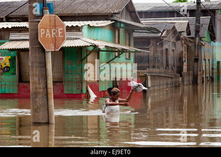 2015 flooding in Brazilian Amazon, woman crosses flooded street in front of a stop sign ( Pare ) at Triangulo Novo - Stock Photo