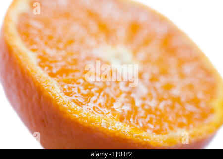 a close up of a fresh Orange fruit cut in half on a white background in a studio environment - Stock Photo