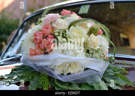 Rose bouquet on wedding car - Stock Photo