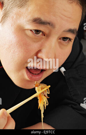 Guy eating glass noodles - Stock Photo