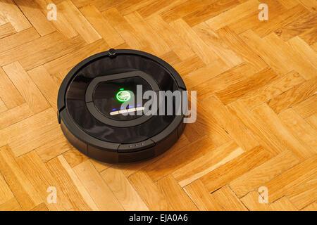 Robotic vacuum cleaner on parquet - Stock Photo