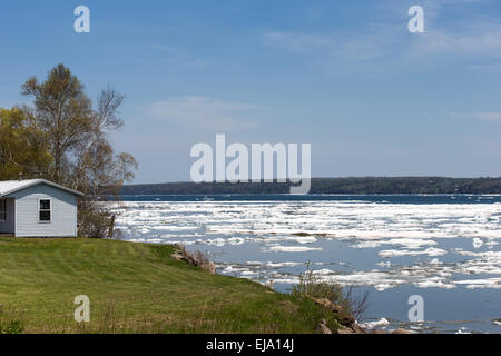 Ice breaking up on a bay in the Spring.   Small house overlooking the scene.  Copy space in upper part of frame. - Stock Photo