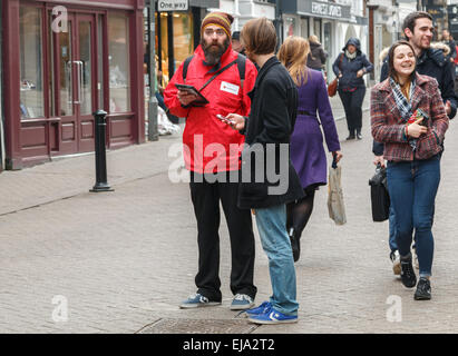Chugger with a big beard from the UK Red Cross society  talking to a potential donor on a city street - Stock Photo