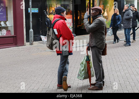 Chugger street collector from the Red Cross Society charity talking to a potential donor on a city street - Stock Photo