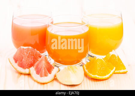 Different juice in glass with pieces of fresh fruits. Vitamin healthy background - Stock Photo