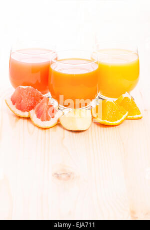 Fresh vitamins juice with different pieces of fruits on wooden table. Healthy beverage background - Stock Photo