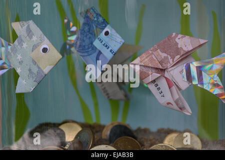 Aquarium with fish money and coins - Stock Photo