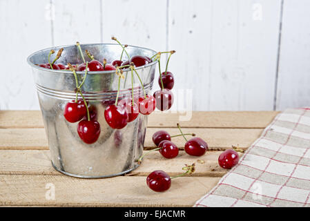 cherries in a small metal bucket on the wooden table - Stock Photo