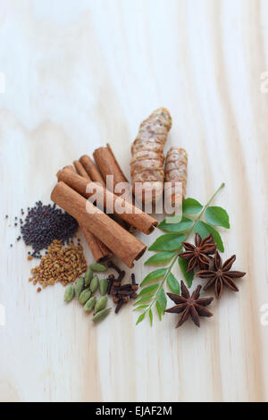 Assorted dried spices including murraya koenigii on a wooden board - Stock Photo
