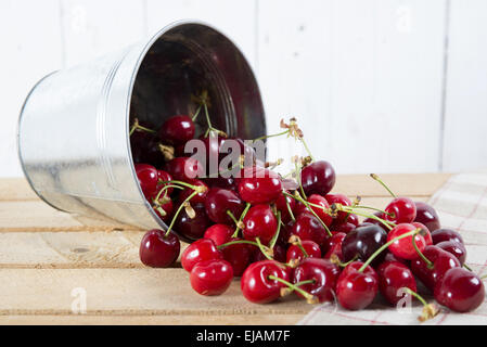 cherries in a small metal bucket overturned on the wooden table - Stock Photo