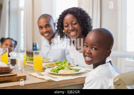 Happy family smiling at camera at lunch - Stock Photo