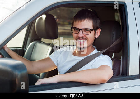 Male european good driver is smiling in his car - Stock Photo