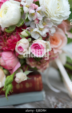 Spring bouquet of pink roses, ranunculus and apple blossoms of the Evereste crabapple tree.